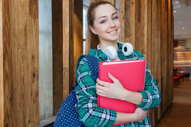 chica con carpeta de estudios y mochila escolar