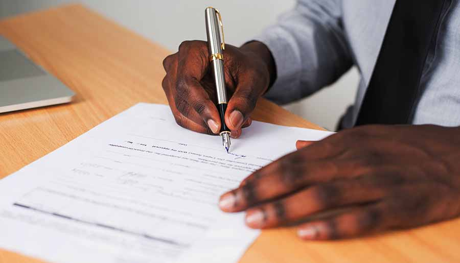 hombre de raza negra firma papeles