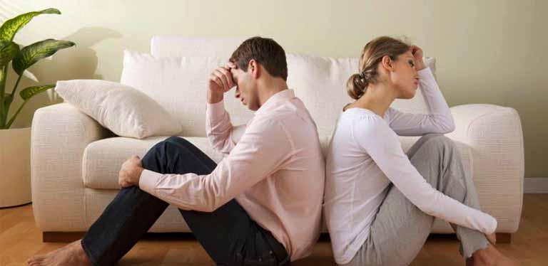 pareja sentada en el suelo de espaldas con la cabeza apoyada en la mano