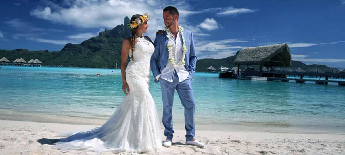 pareja recien casados pasean por una playa del extranjero