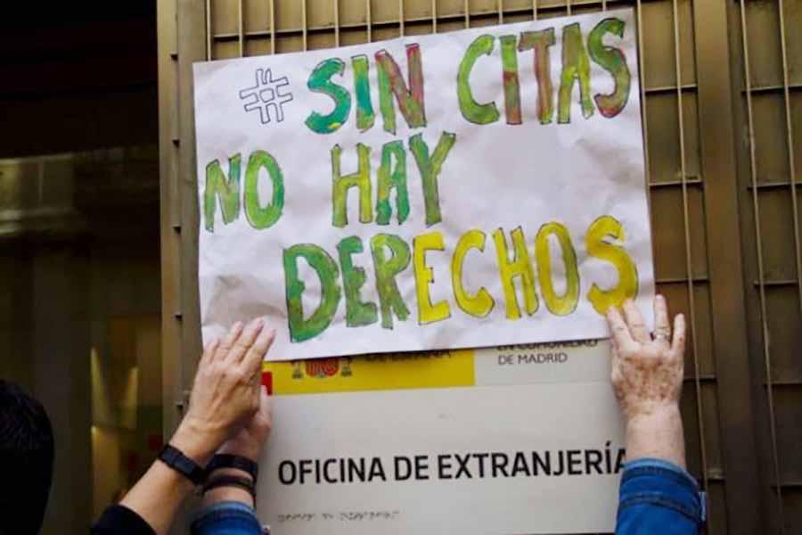manos enganchando un cartel que dice sin citas no hay derecos en la pared de la oficina de extranjería