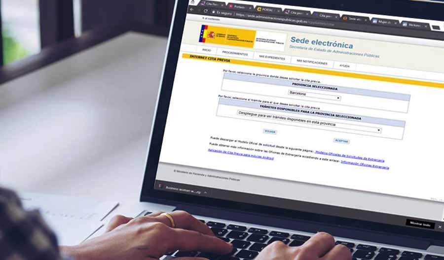 persona en un ordenador solicita cita previa en la sede electronica de gobierno de espana