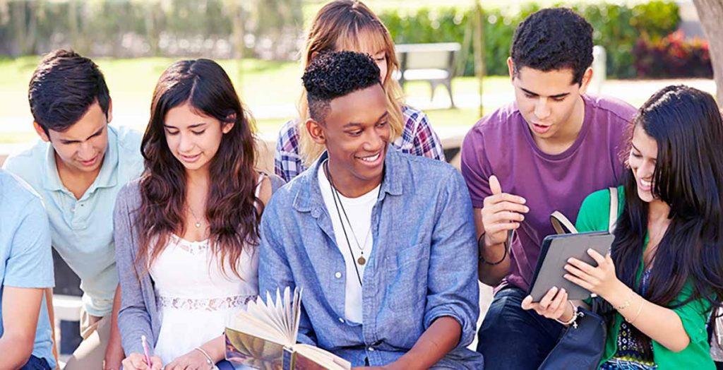 grupo de estudiantes extranjeros haciendo deberes y leyendo libros en un parque
