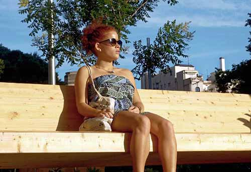 mujer extranjera joven sentada en banco