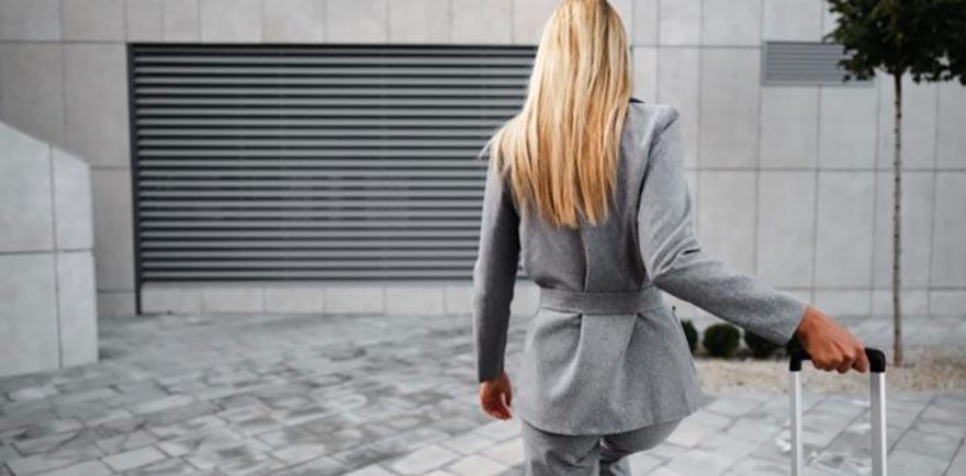 Chica con maleta andando por la calle