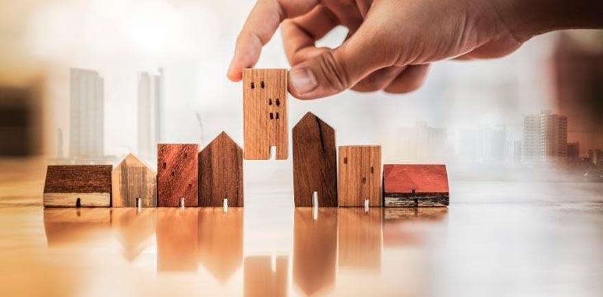 Mano poniendo casas en miniatura de madera